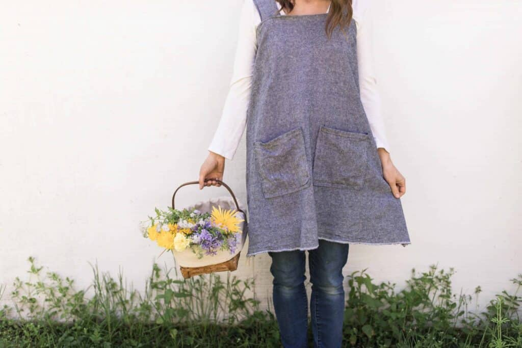 women with a DIY apron holding a basket of flowers