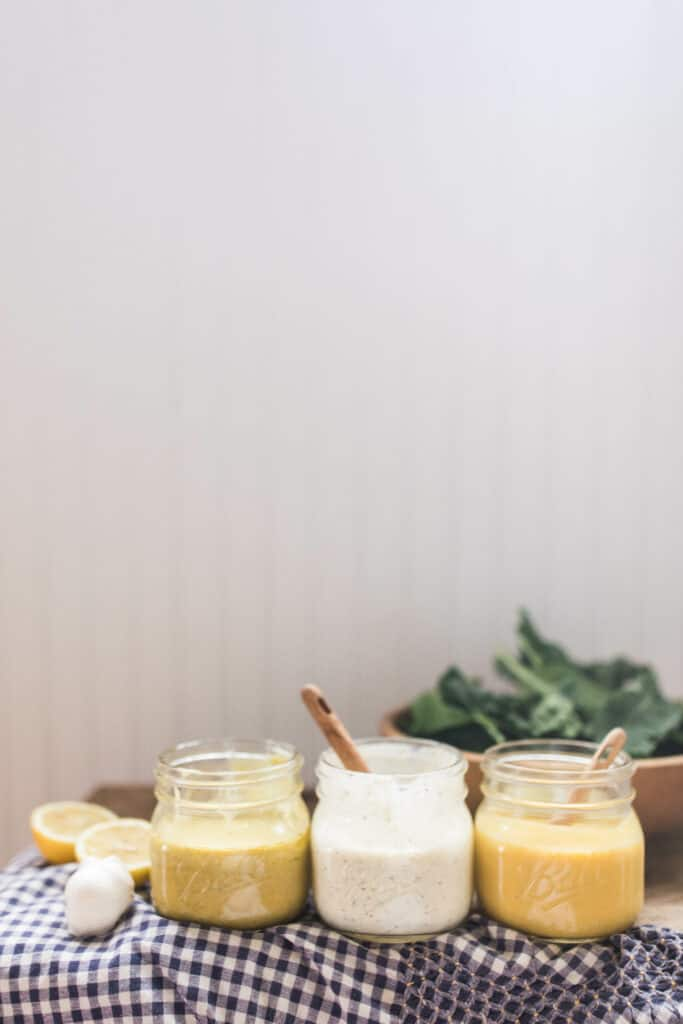 3 homemade salad dressings in glass jars on a wood countertop with a blue and white checked towel and a bowl of salad behind them
