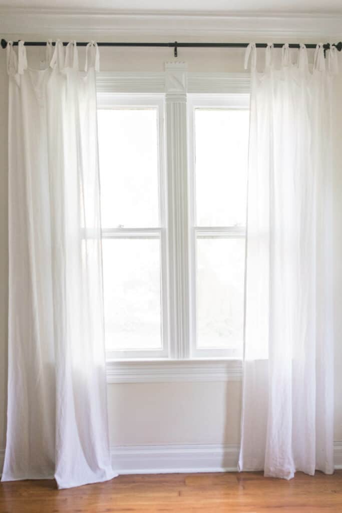 white tie top curtains hanging on a black curtain rod - how to make curtains tutorial