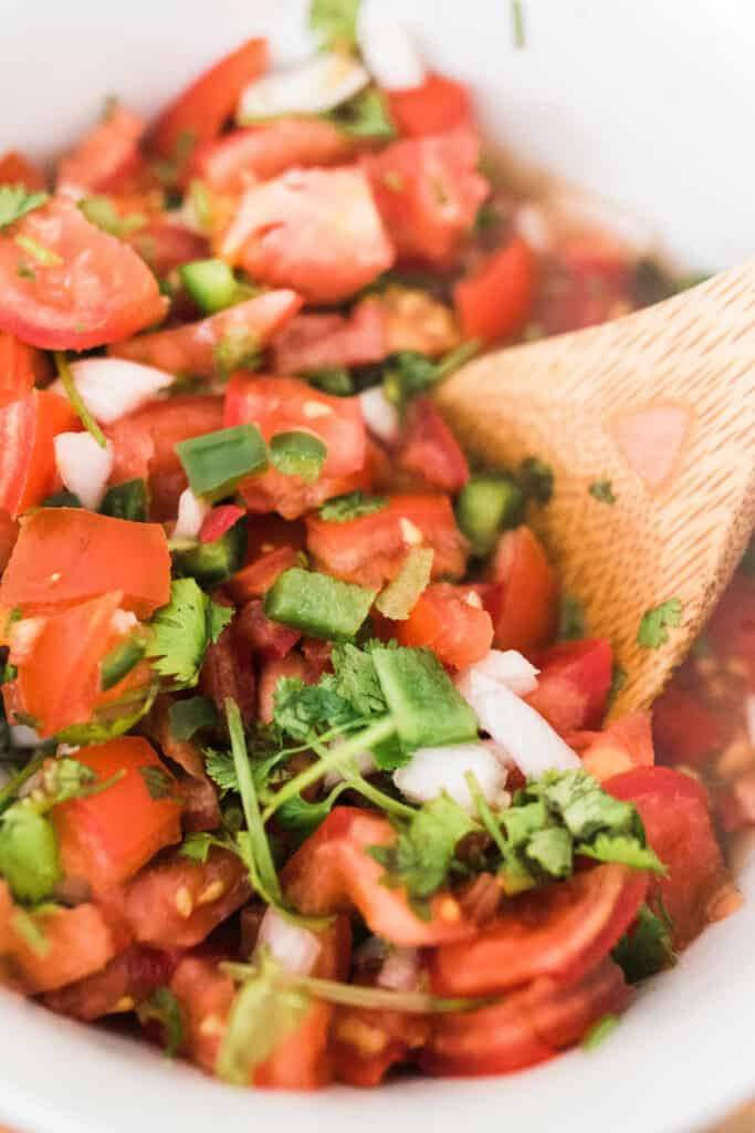 close up of fermented salsa in a white bowl with a wooden spoon