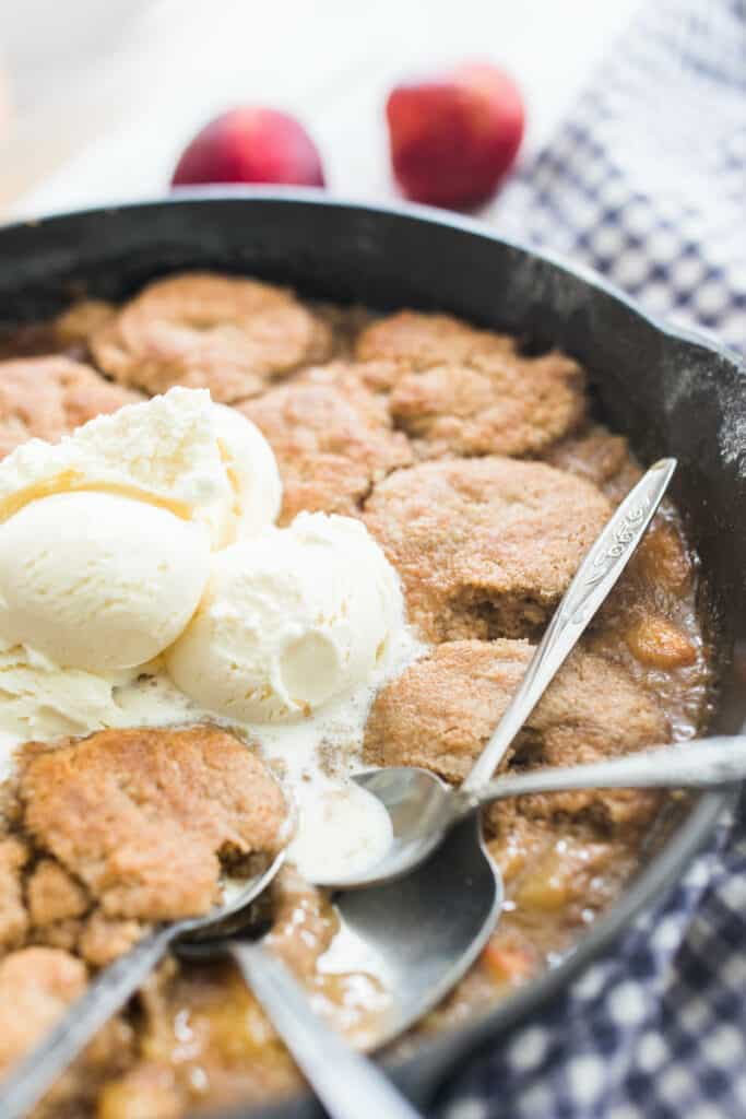 up close picture of sourdough peach cobbler topped with ice cream in a cast iron skillet