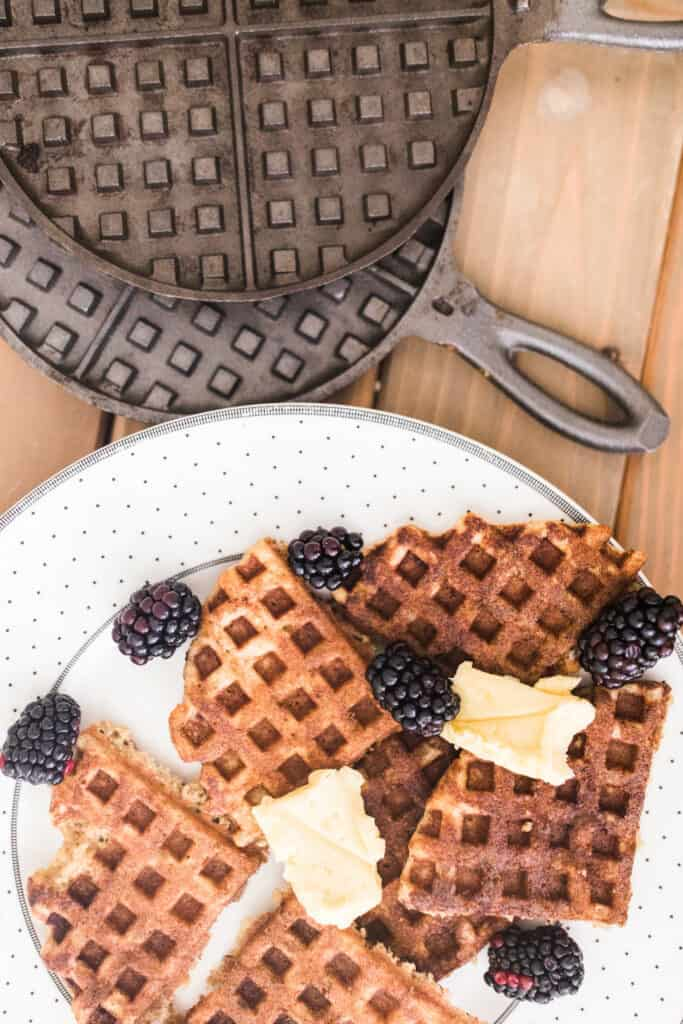 sourdough waffles topped with blackberries and butter on a white plate with cast iron waffle maker behind it.