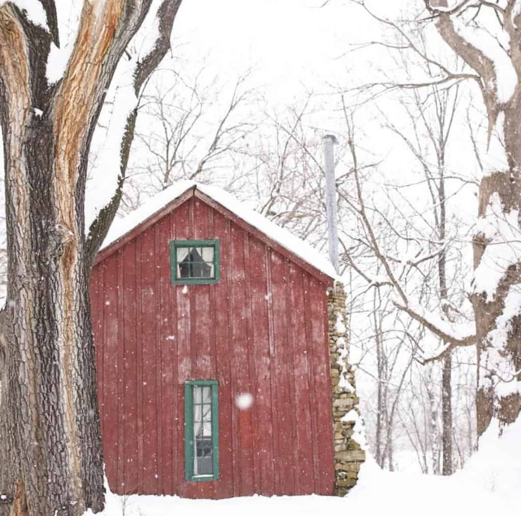 red farmhouse cottage with green trim on a snowy winter day