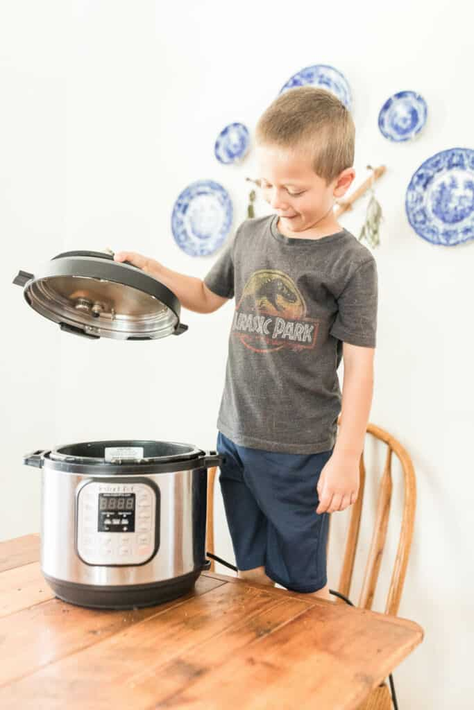 little boy standing on a chair holding the lid to the Instant Pot