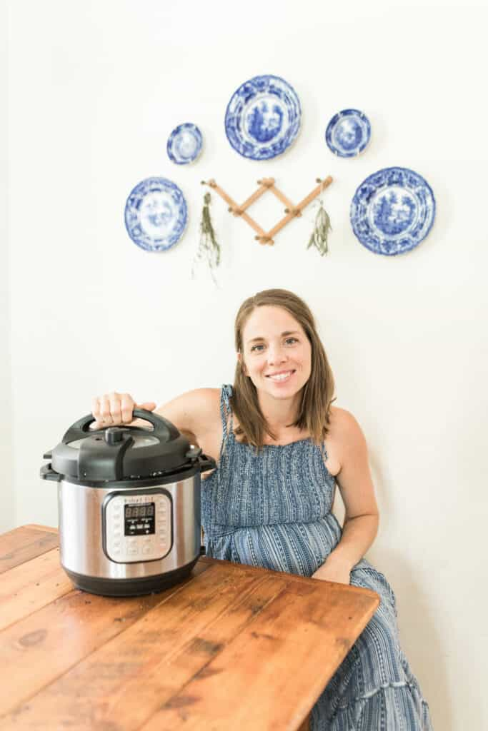 women sitting at a table with her hand touching the lid of the lid of the Instant Pot