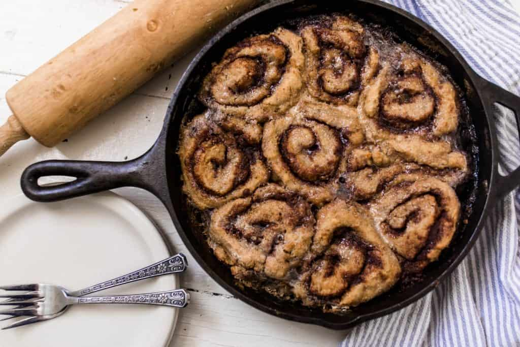 sourdough cinnamon rolls fresh out of the oven in a cast iron skillet on a blue and white stripped towel with a rolling pin and a white plate to the left