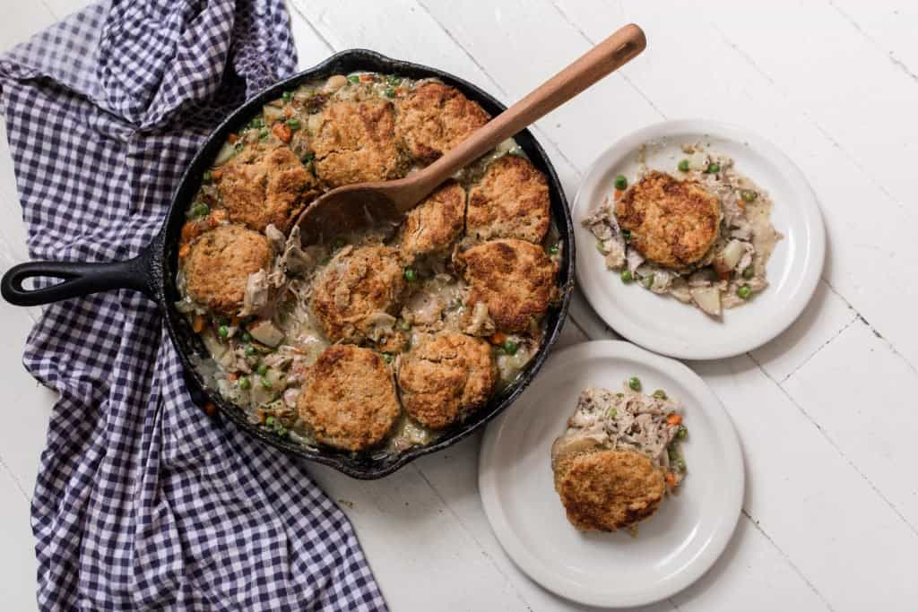 baked sourdough chicken pot pie in a cast iron skillet with two plates to the right with a serving of pot pie on each