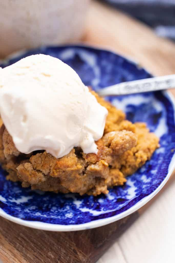 antique white and blue plate with a slice of pumpkin cobbler with a large scoop of ice cream