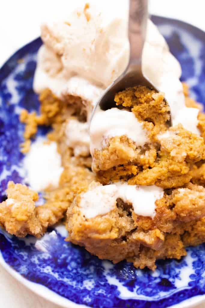 spoon scooping into a blue and white bowl full of spiced sourdough pumpkin cobbler topped with homemade ice cream