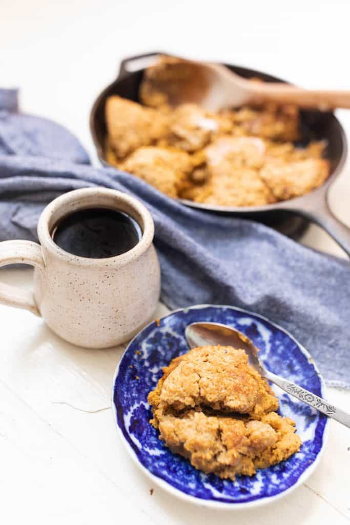 bowl of pumpkin cobbler with a cup of coffee a blue towel and skillet containing remaining sourdough cobbler behind