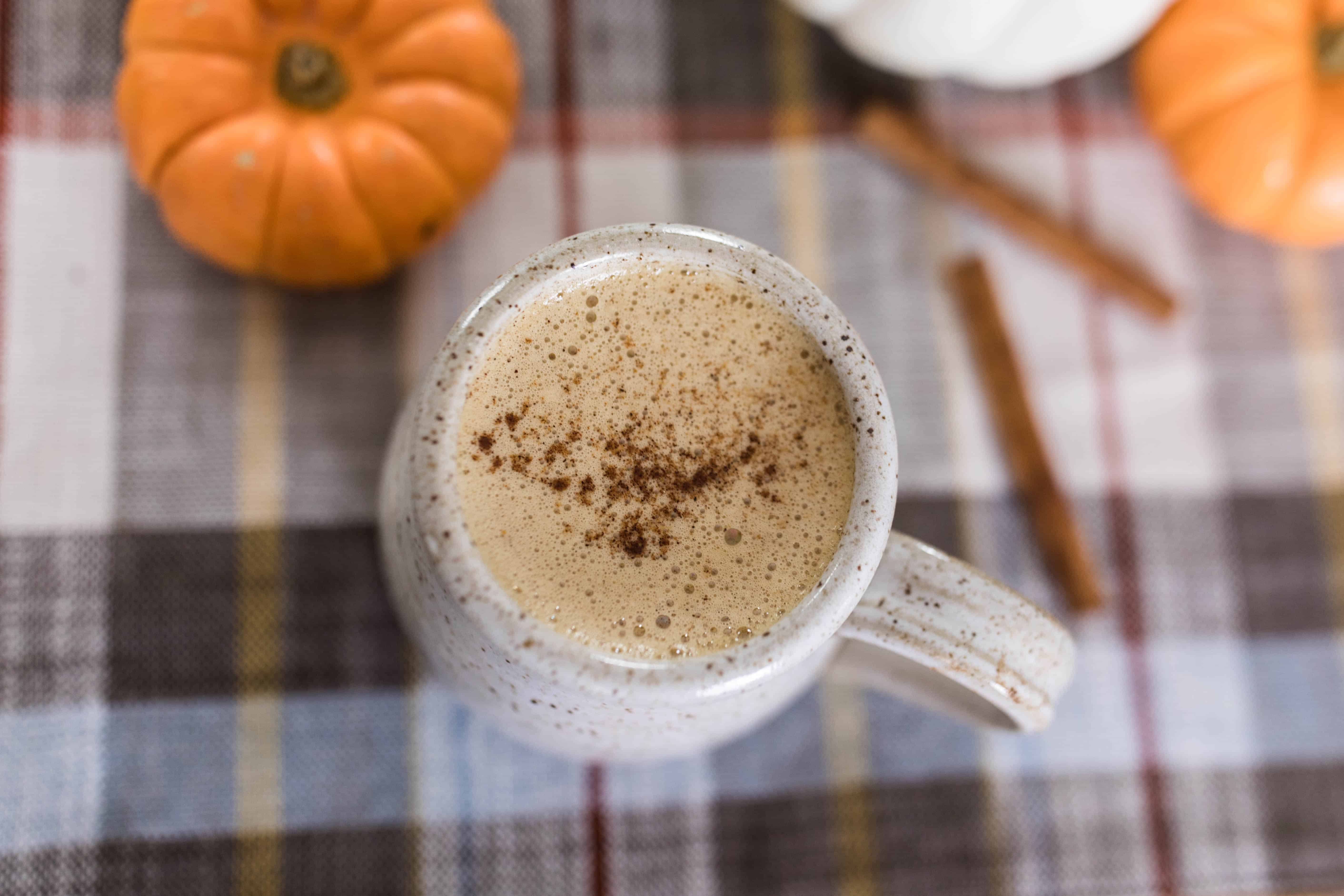 overhead shot of bulletproof pumpkin spice latte sprinkled with pumpkin spice on top in a stoneware mug on a plaid napkin with mini pumpkins around