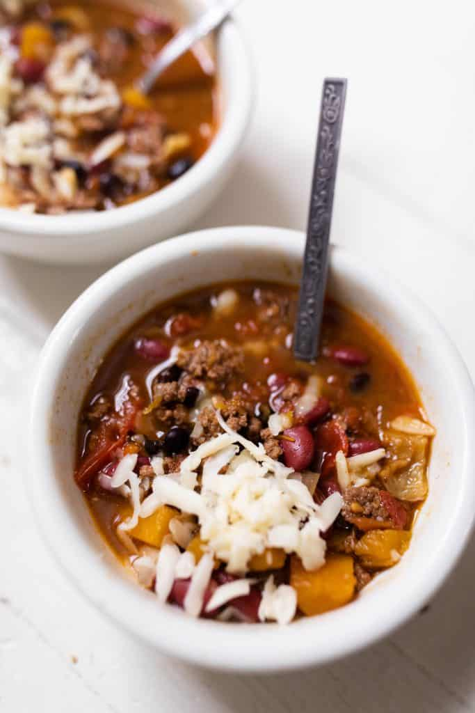 pumpkin chili in a white bowl topped with fresh grated cheese with a spoon in the stew