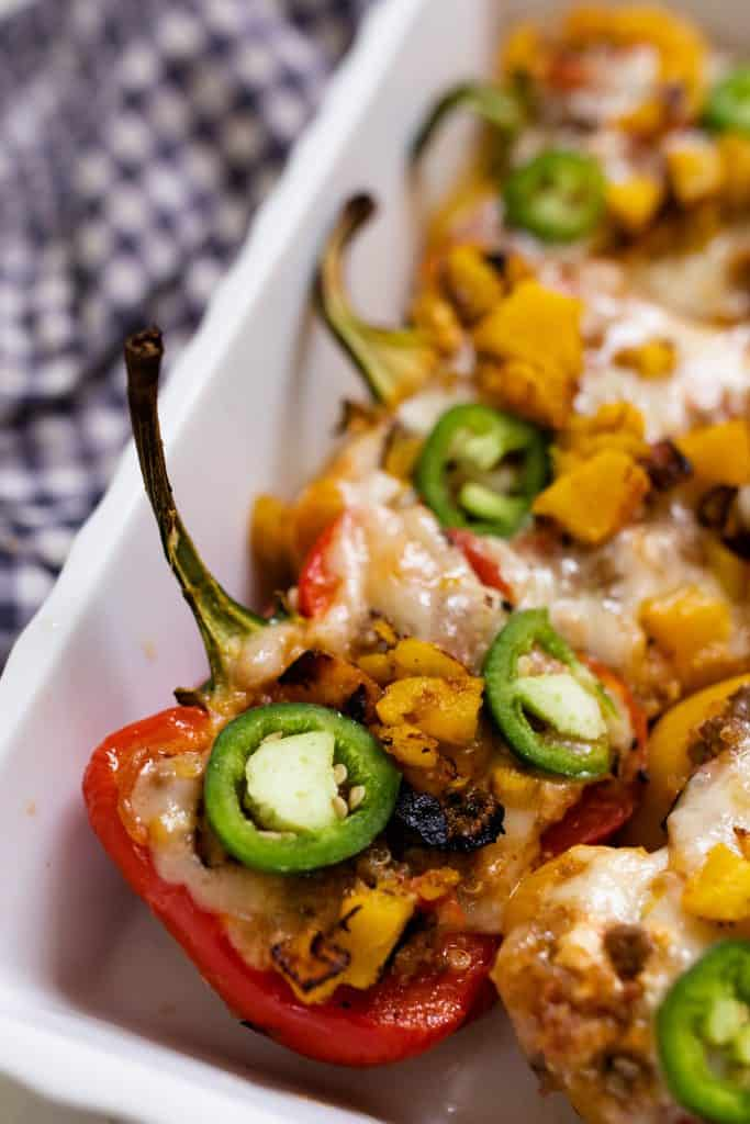 baking dish full of stuffed bell peppers with ground beef and topped with cheese and jalepenos