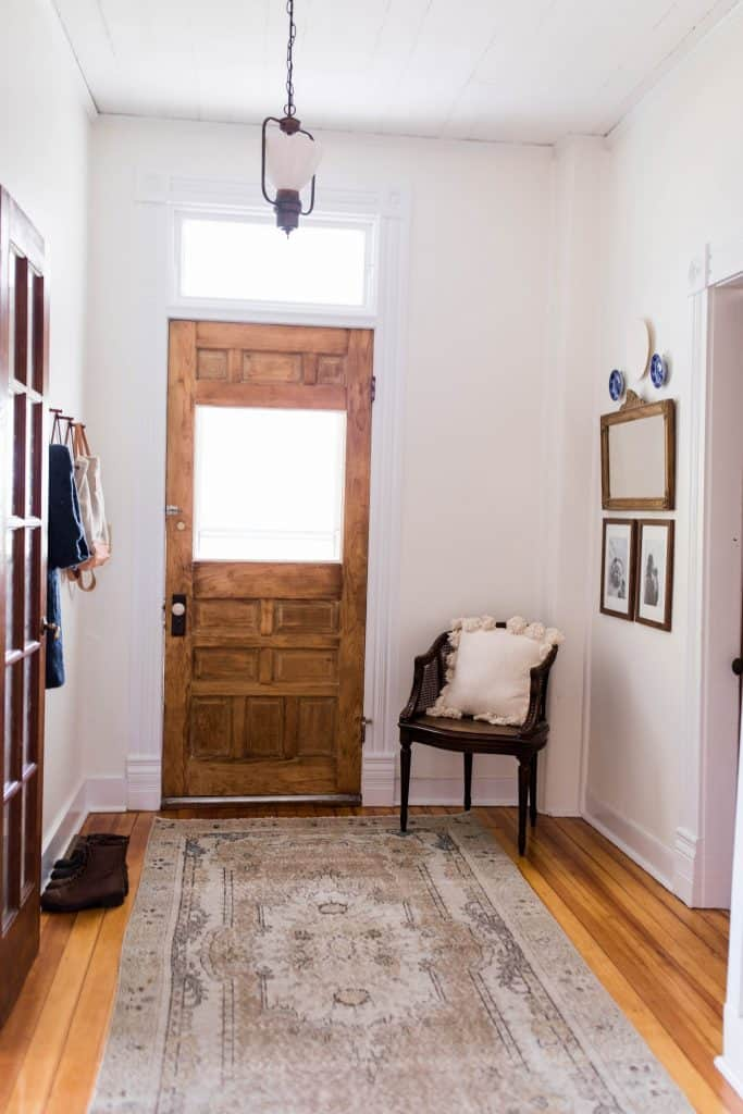 Farmhouse entryway with Victorian features including a original wooden door, turkey rug over beautiful refinished floors, and farmhouse decor
