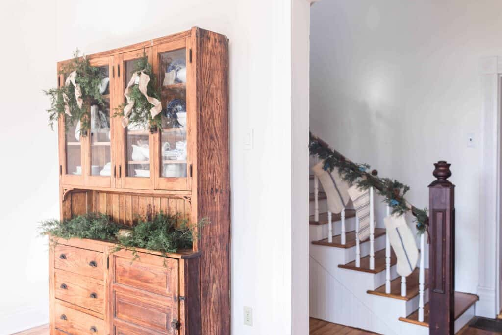 side view of wooden hutch decorated with greenery, burlap ribbon and bells for the holidays. Also there is a partial view of the staircase covered with greenery garland and grain-sack stockings.
