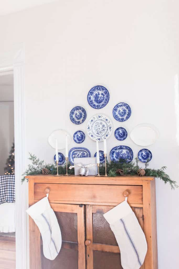 antique pie safe topped with fresh greenery. Antique flow blue plates hang above the pie save. Stocking hang from the knobs of the pie safe