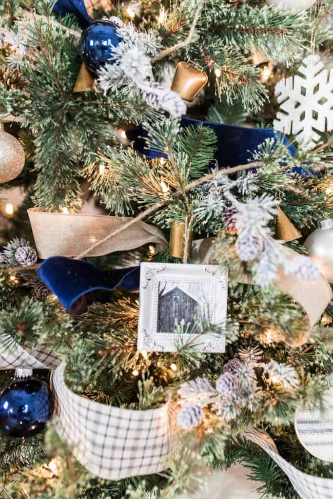 handmade Christmas ornaments hanging on a blue and white decorated tree