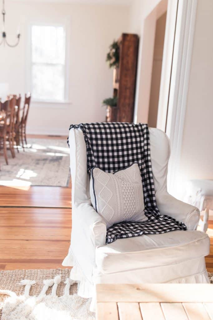 winged back chair covered in a blue and white checked flannel blanket and topped with a sweater pillow