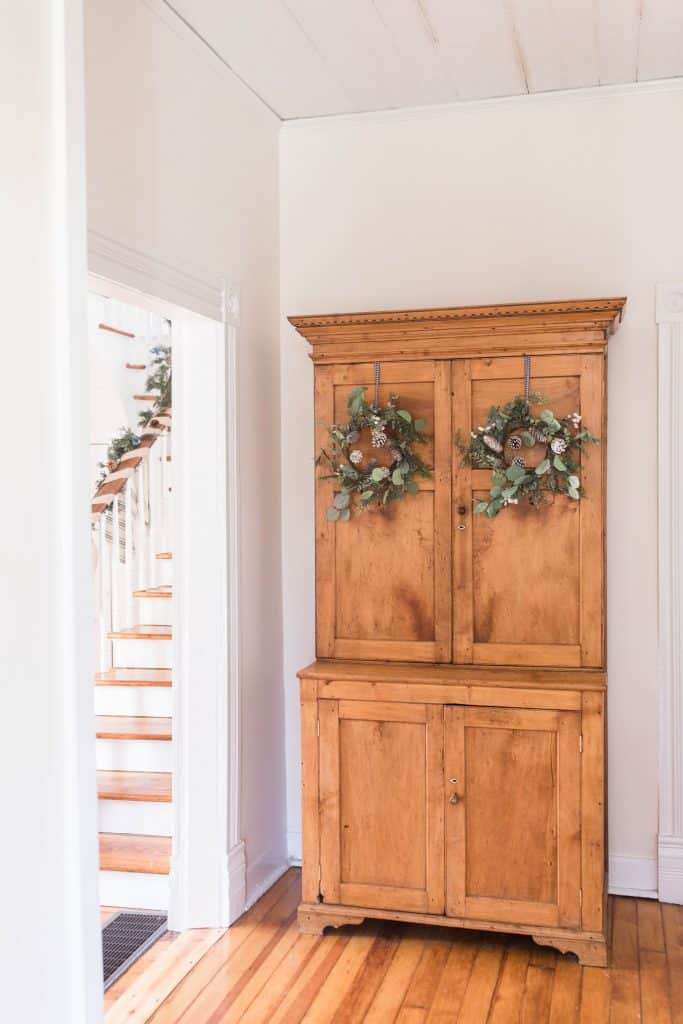 antique wood cabinet with two wreaths hung on the doors