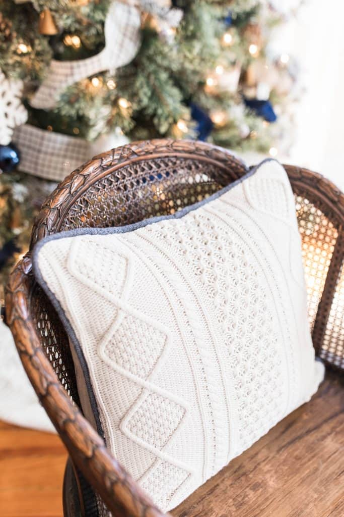white sweater pillow on a wood chair with a Christmas Tree in the background