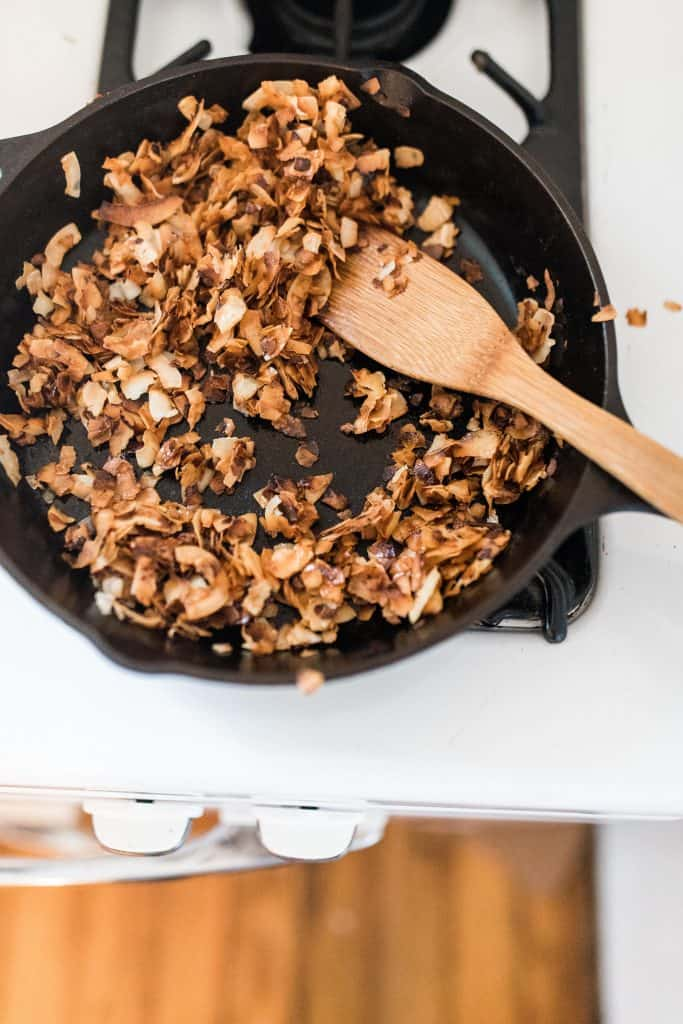 toasting shredded coconut in a cast iron skillet with a wooden utensil