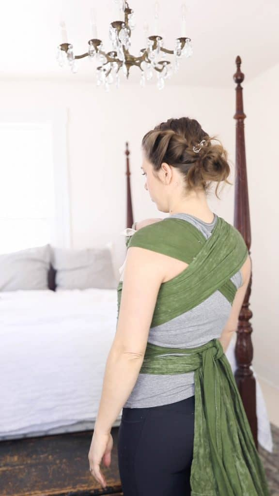 a women wearing a green DIY Mei Tai . She is showing the straps crisscrossing across the back and tied at the waist in the back.