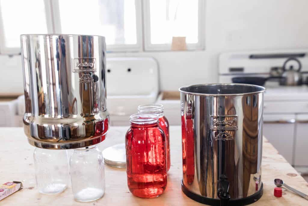Berkey Water filter over two clean mason jars with two half gallon mason jars to the right with red dye and the bottom canister to the right - Berkey red dye test