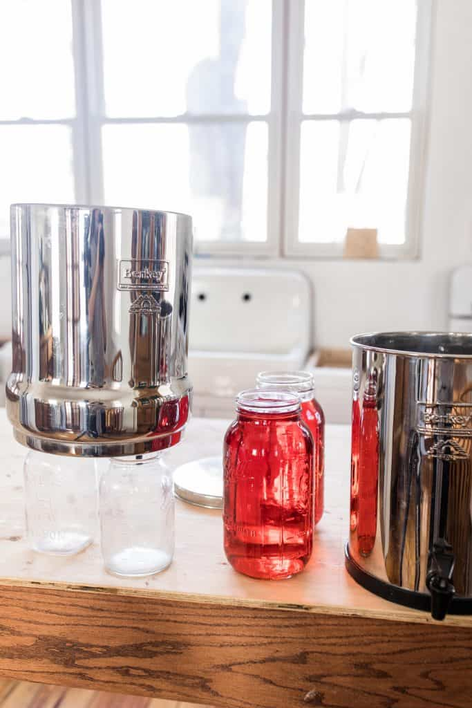 Berkey Water filter over two clean mason jars with two half gallon mason jars to the right with red dye.