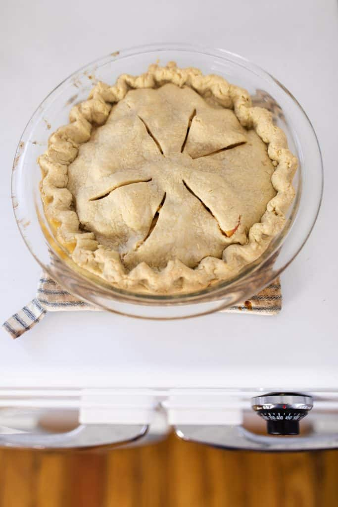homemade apple pie straight out of the oven cooking on top of a vintage oven