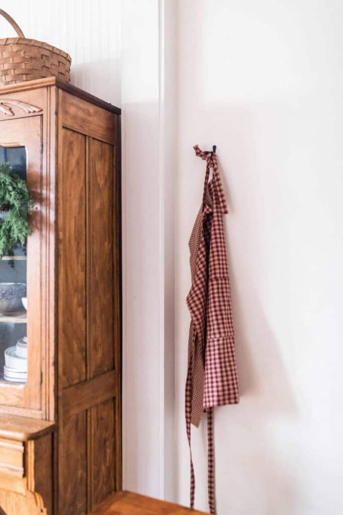 diy reversible apron on a hook next to a wooden china cabinet with a wreath
