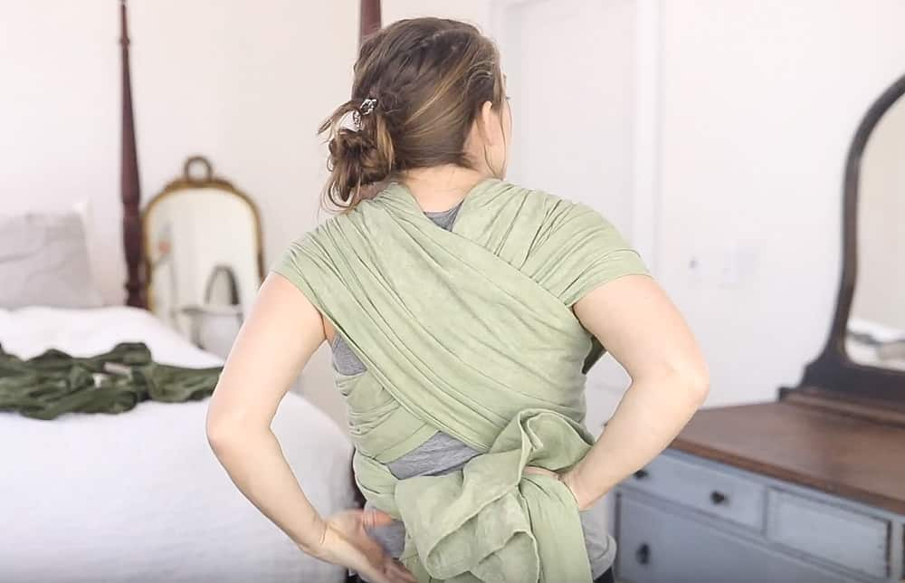 women tying woven wrap tails behind her back to create a secure wrap