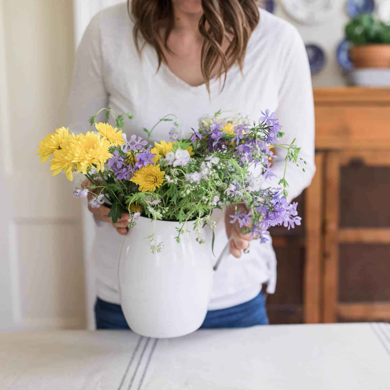 Woman holding white vase with yellow and purple flowers
