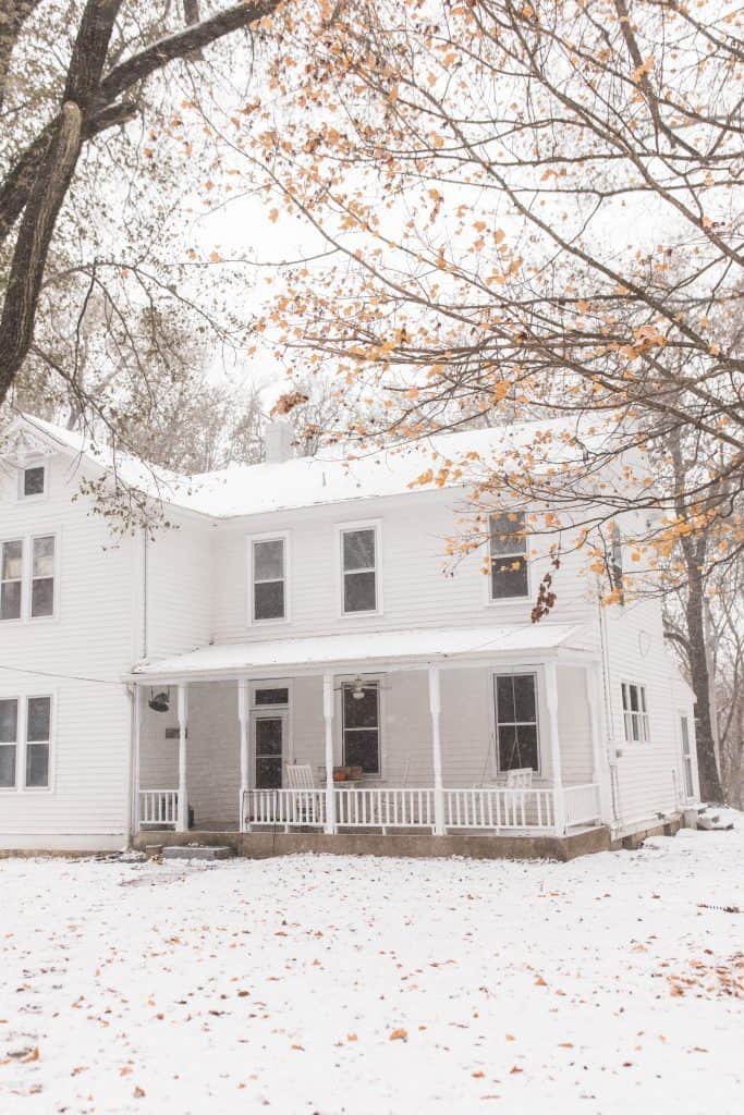 white victorian farmhouse in the snow front view