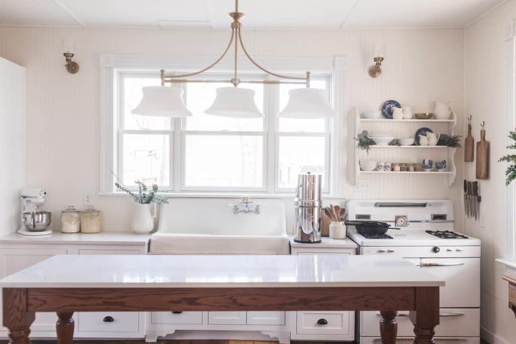 victorian farmhouse kitchen with long work table with quarts countertop. 3 pendant brass light fixture hangs over the table