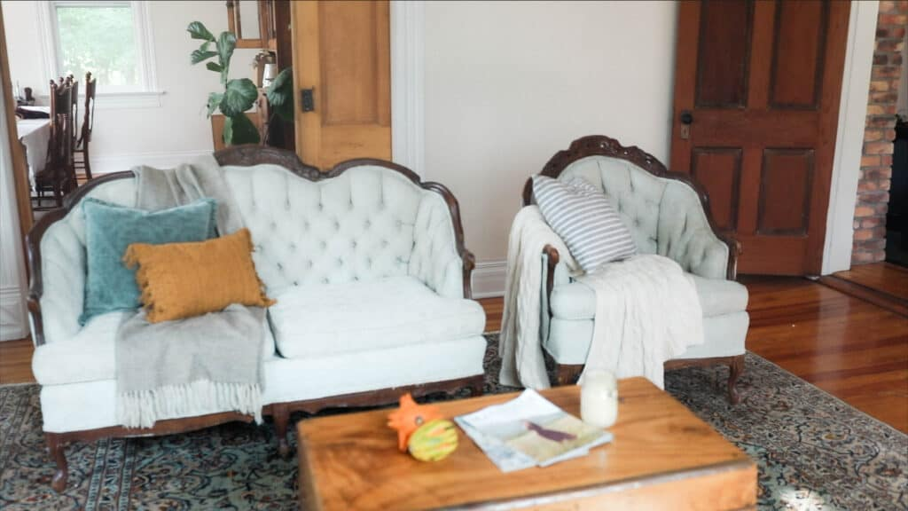 chalk painted antique victorian love seat and chair with a throw pillows and blankets