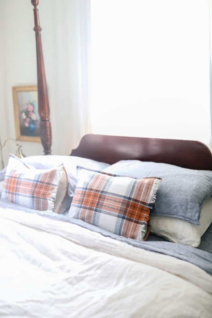 blue and orange plaid pillows on a bed with white and blue linen sheets