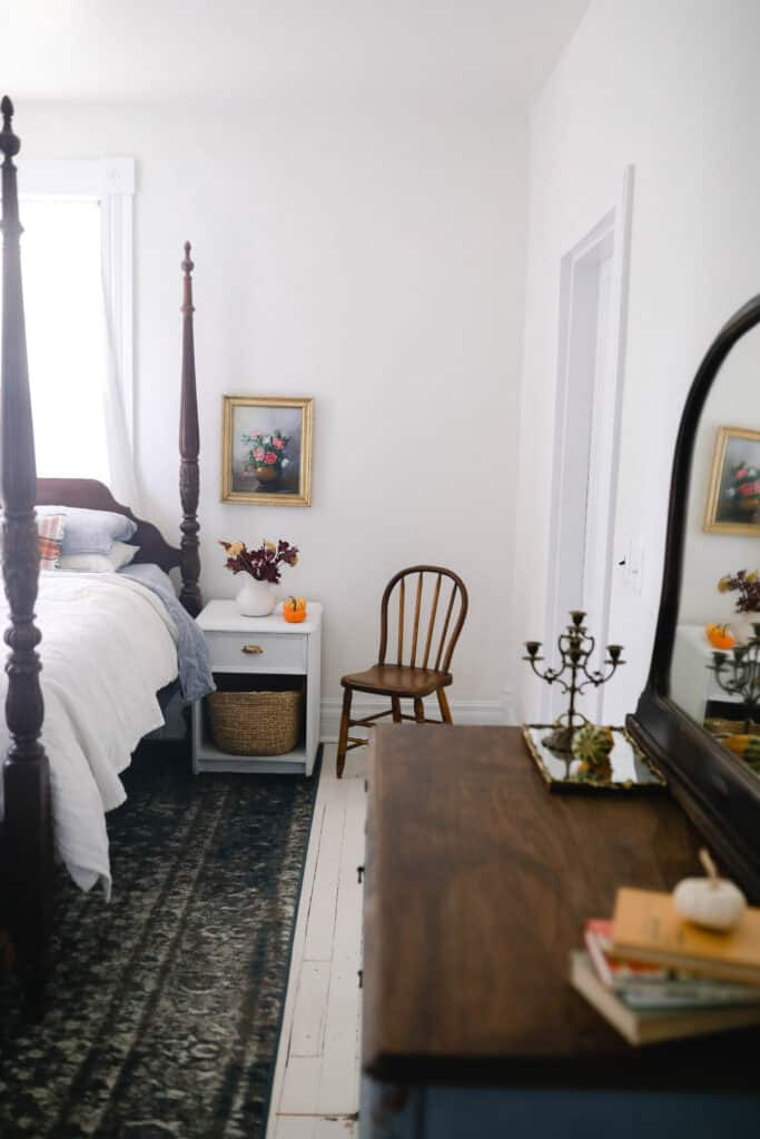 orange and brown books stacked on a dresser with a small white pumpkin on top. Fall florals in a white vase and a pumpkin on a night stand and fall linens on a antique bed.