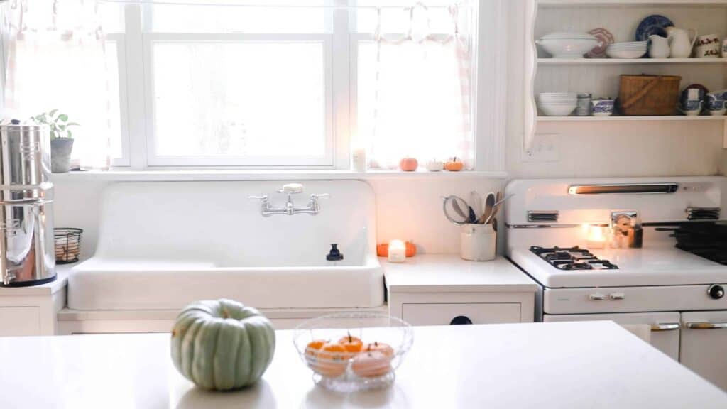 white victorian farmhouse kitchen with pumpkins set in a basket on the island and resting on the window sill