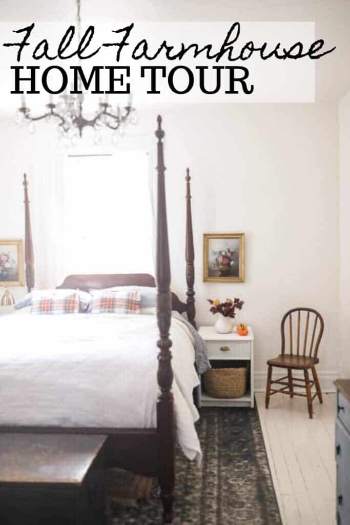 victorian farmhouse bedroom with orange plaid pillows on top a white linen duvet. A night stand to the right has dried fall florals and pumpkins