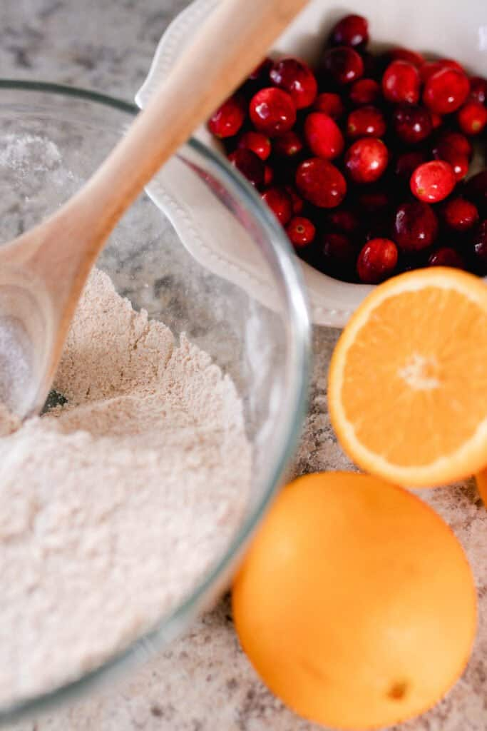 bowl of dry ingredients with sliced oranges and a bowl of cranberries behind
