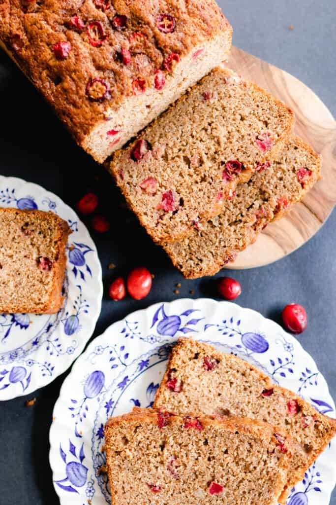 Cranberry orange quick bread on two white and blue plates with the loaf on a cutting board