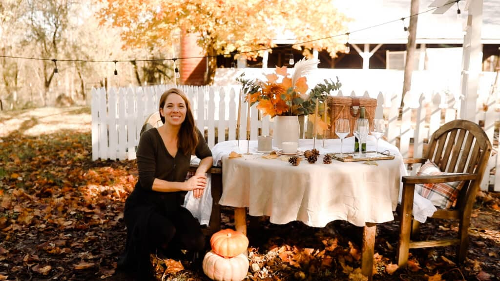 women sitting at a table set for a fall tablescape with dried leaves, pinecones, and beeswax candles next to a white picket fence and a barn.