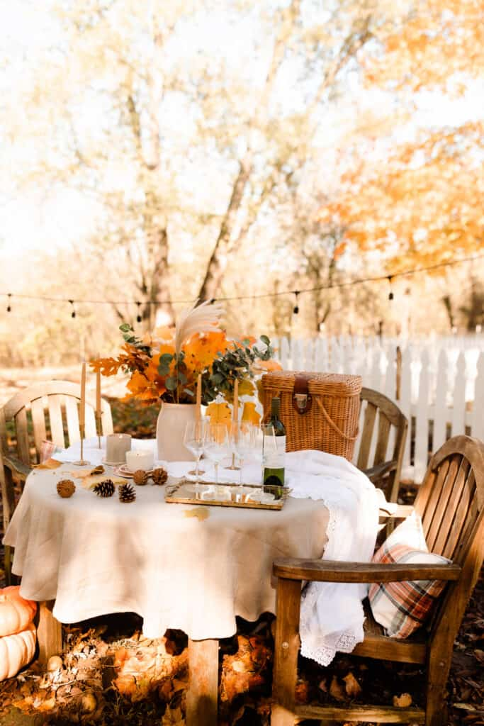 fall table scape outside next to a white picket fence.