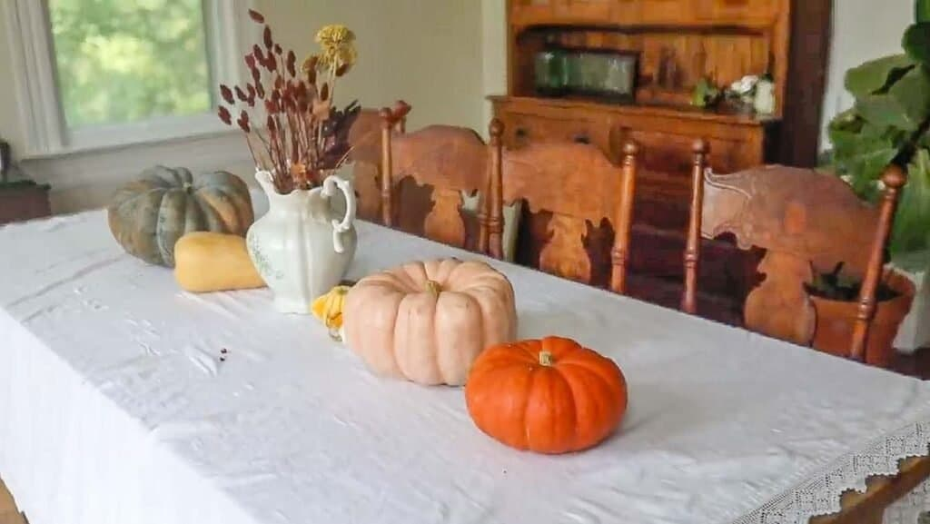 pumpkins on a table with a white linen table cloth