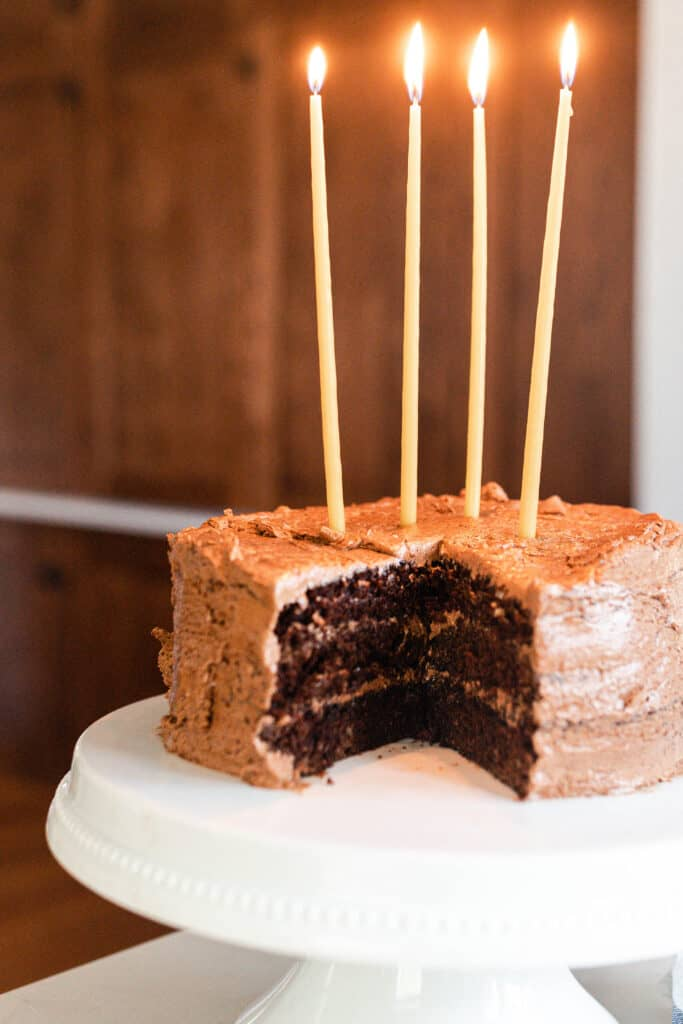 chocolate cake with chocolate frosting with 4 long candles on a white cake stand