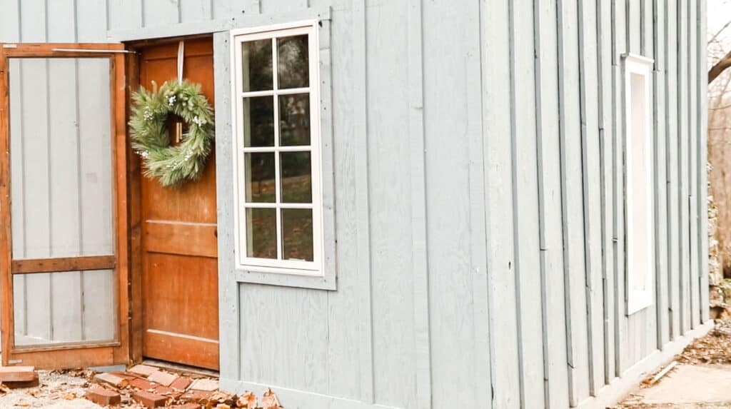 faux greenery christmas wreath on a antique cottage door