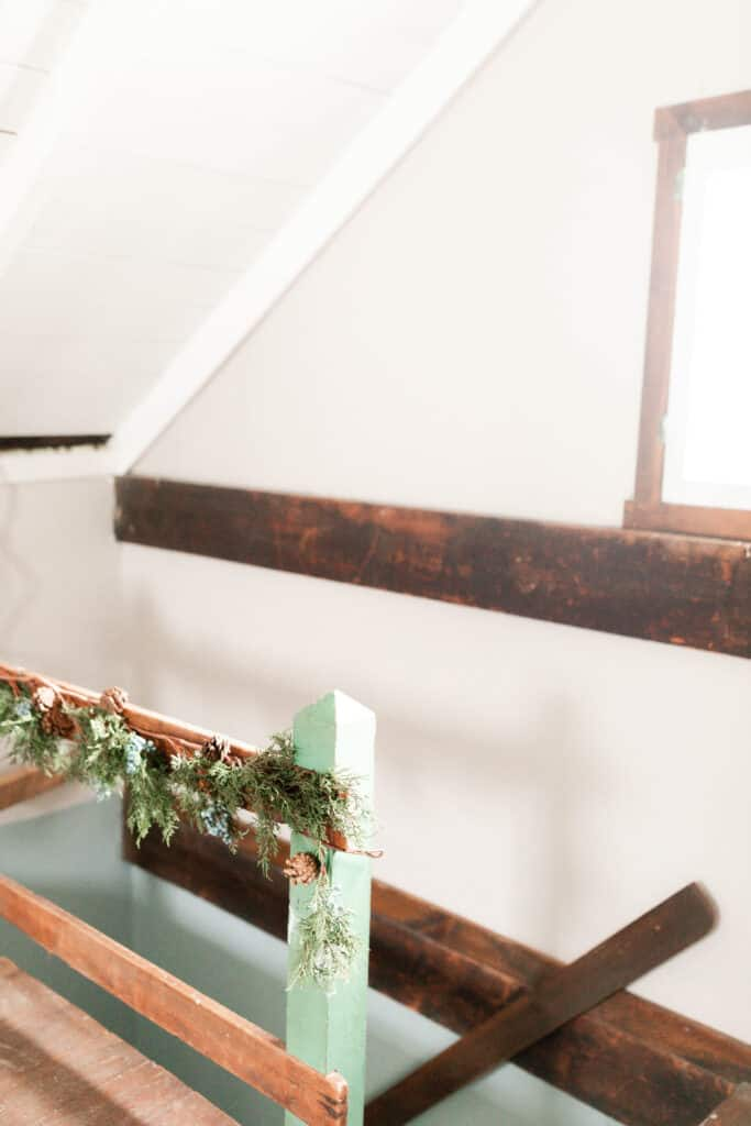garland hung on a green and wood bannister