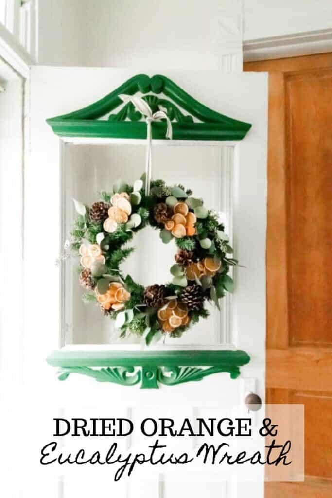 Dried eucalyptus wreath with sliced dried oranges and pinecones hanging with ribbon on a vintage white and green door