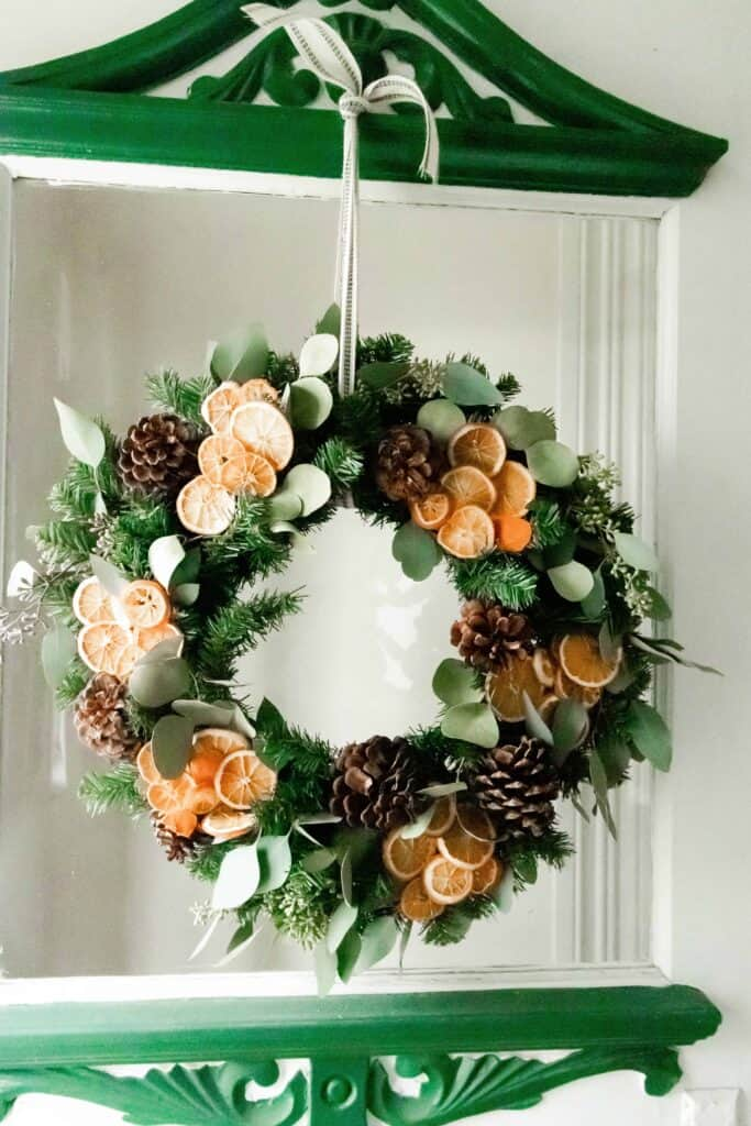 Dried orange and eucalyptus Christmas wreath hanging on a vintage white and green door with glass