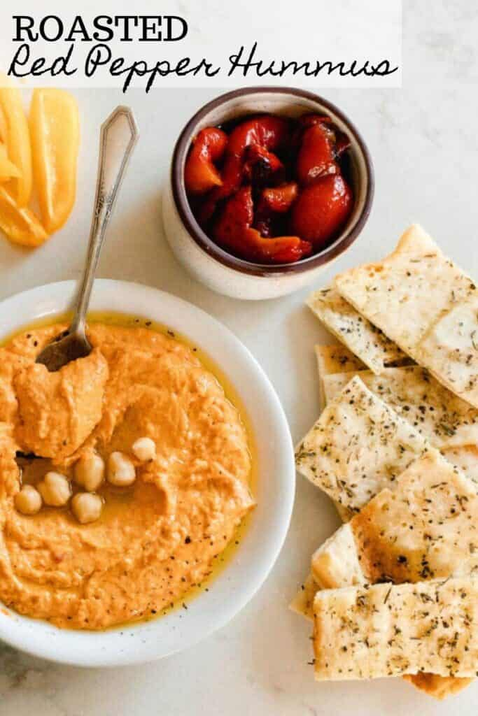 bowl of roasted red pepper hummus topped with chickpeas with a jar of roasted red peppers back in oil and sourdough flat bread to the right
